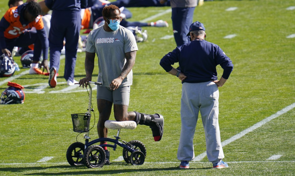 Injured Denver Broncos outside linebacker Von Miller, left, chats with head coach Vic Fangio as players stretch during an NFL football practice Wednes...