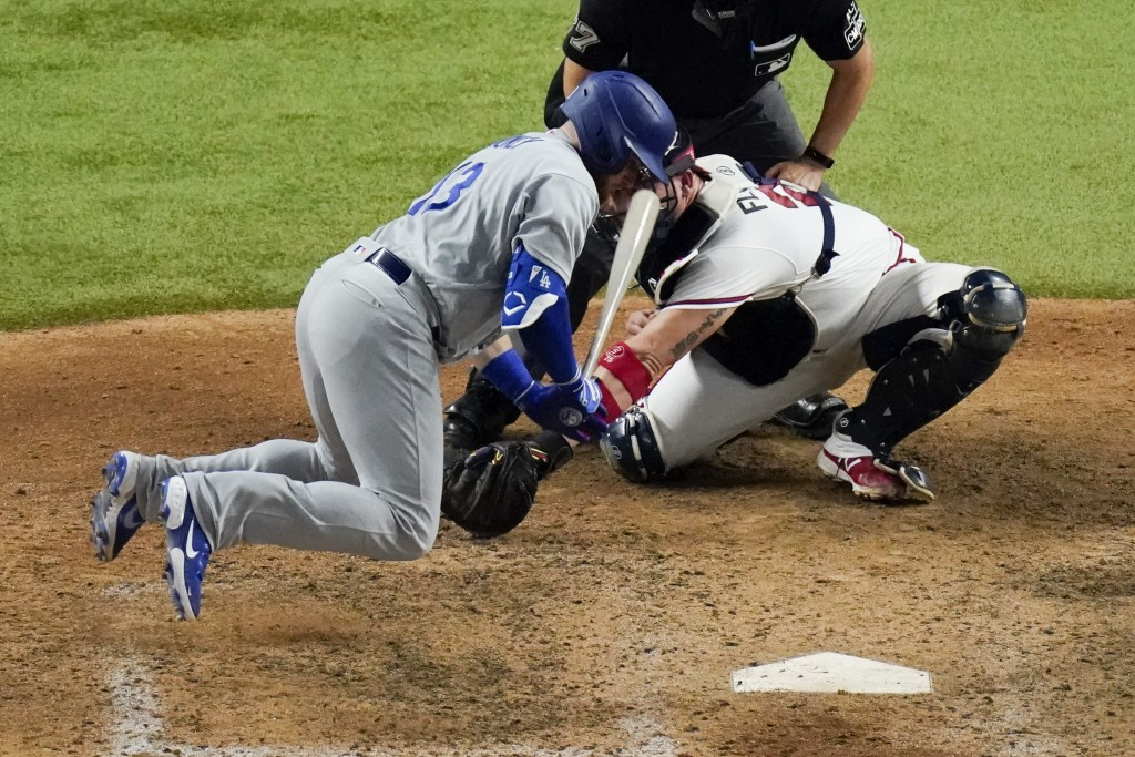 Los Angeles Dodgers' Max Muncy jumps out of the way of a pitch during the eighth inning in Game 3 of a baseball National League Championship Series ag...