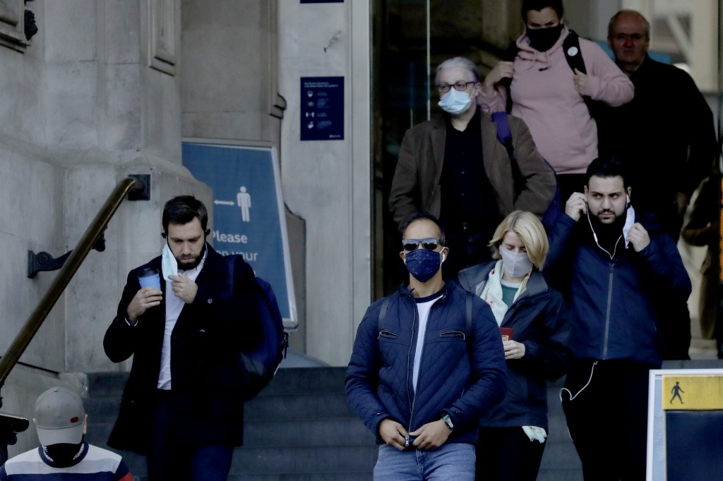 People walk down the steps of the main entrance of Waterloo train station, at which point they are allowed to remove their face coverings, in London, ...