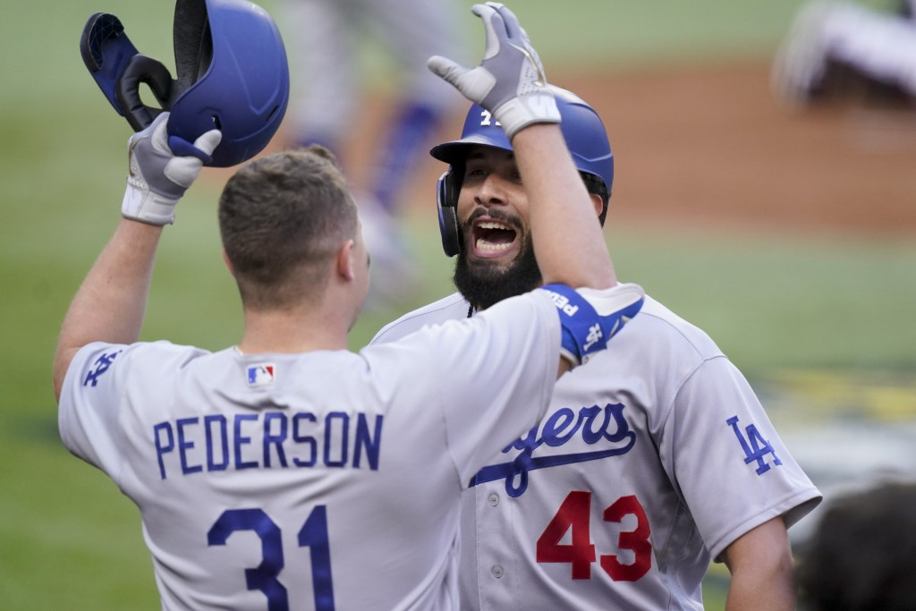 Los Angeles Dodgers Edwin Rios celebrates his home run with Joc Pederson against the Atlanta Braves during the first inning in Game 3 of a baseball Na...