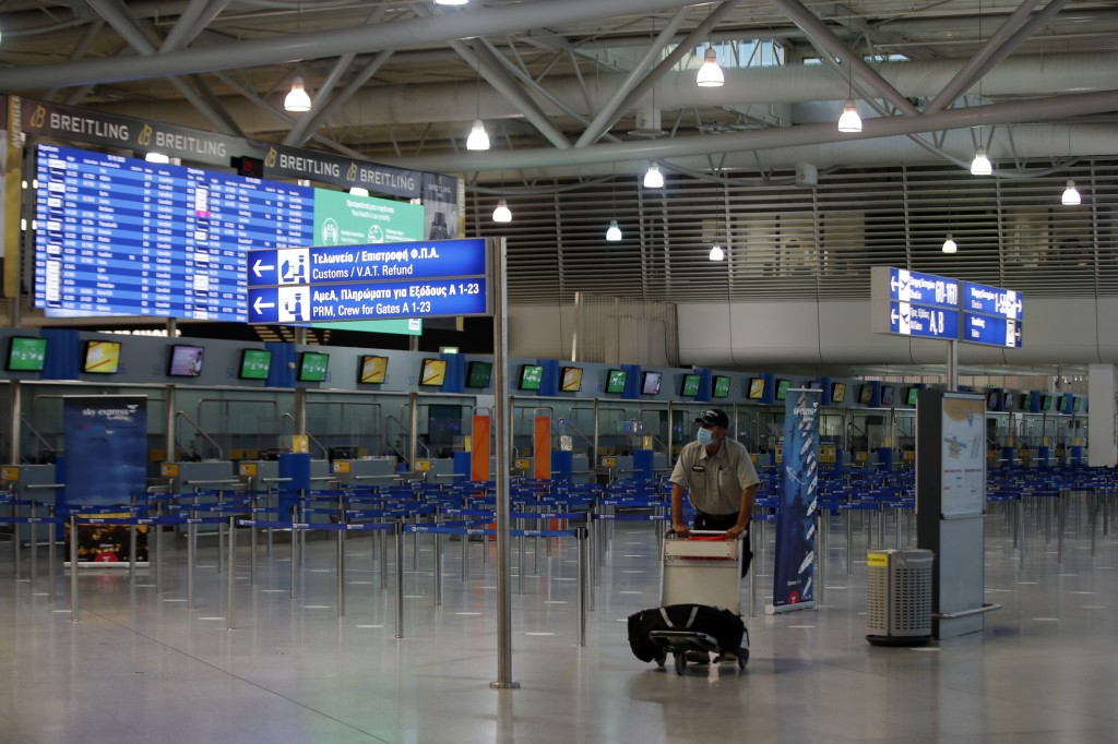 A passenger wearing a face mask to prevent the spread of the new coronavirus, walks at the empty Eleftherios Venizelos International Airport during a ...