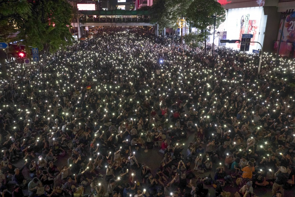 Pro-democracy protesters hold up flashlights on the phones during the pro-democracy rally occupied the main road in the central business district in B...