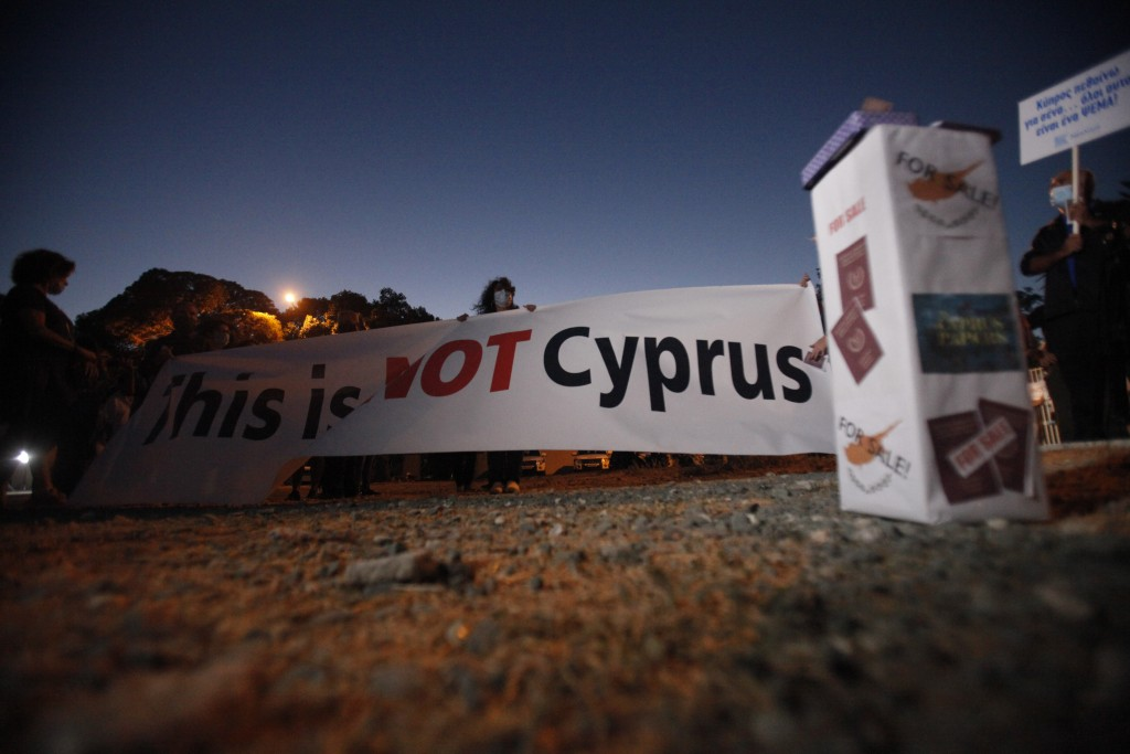 "A protester holds a banner reading ""This is Not Cyprus"" as a box right shows Cyprus Passports the Cyprus flag reading ""For Sale"" during a demonstratio..."