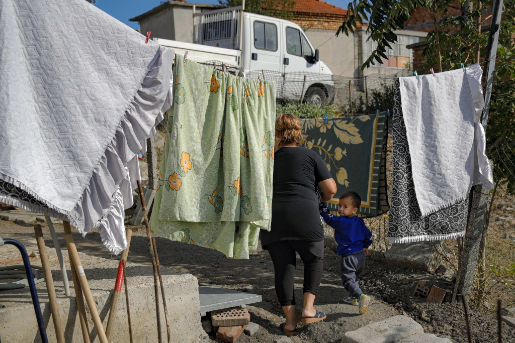 Azime Ali Topchu, 48, a Bulgarian Roma woman, walks with one of her nephews in a village on the outskirts of Burgas, Bulgaria, Monday, Sept. 28, 2020....