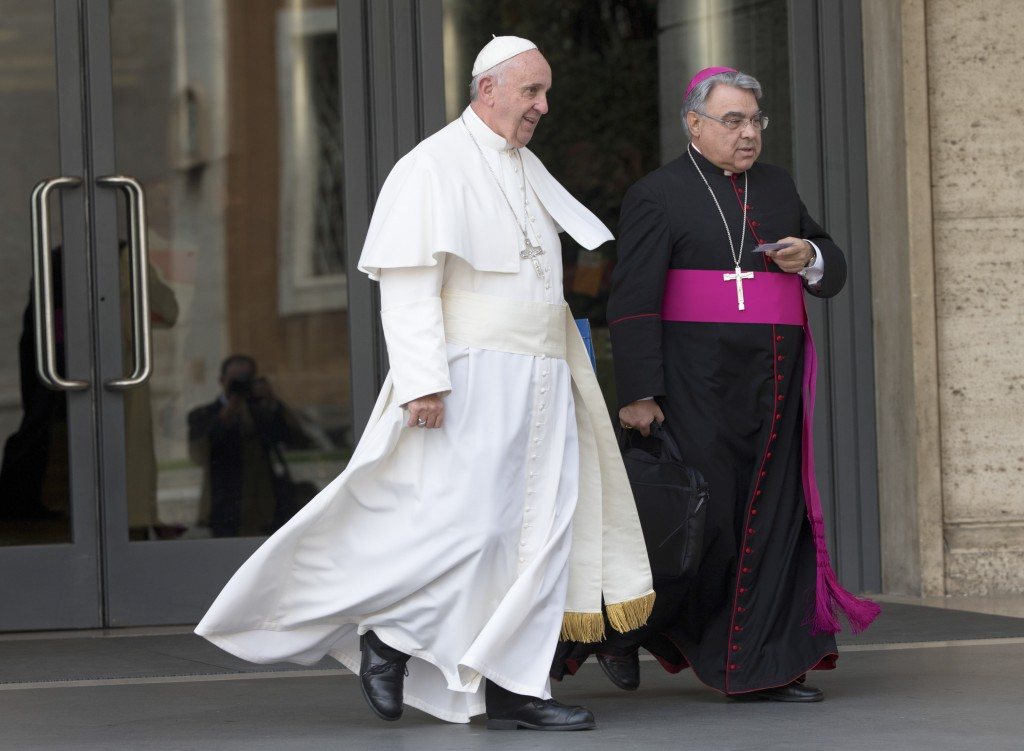 FILE - In this Oct. 5, 2015 file photo, Pope Francis, flanked by bishop Marcello Semeraro, leaves at the end of a morning session of the Synod of bish...
