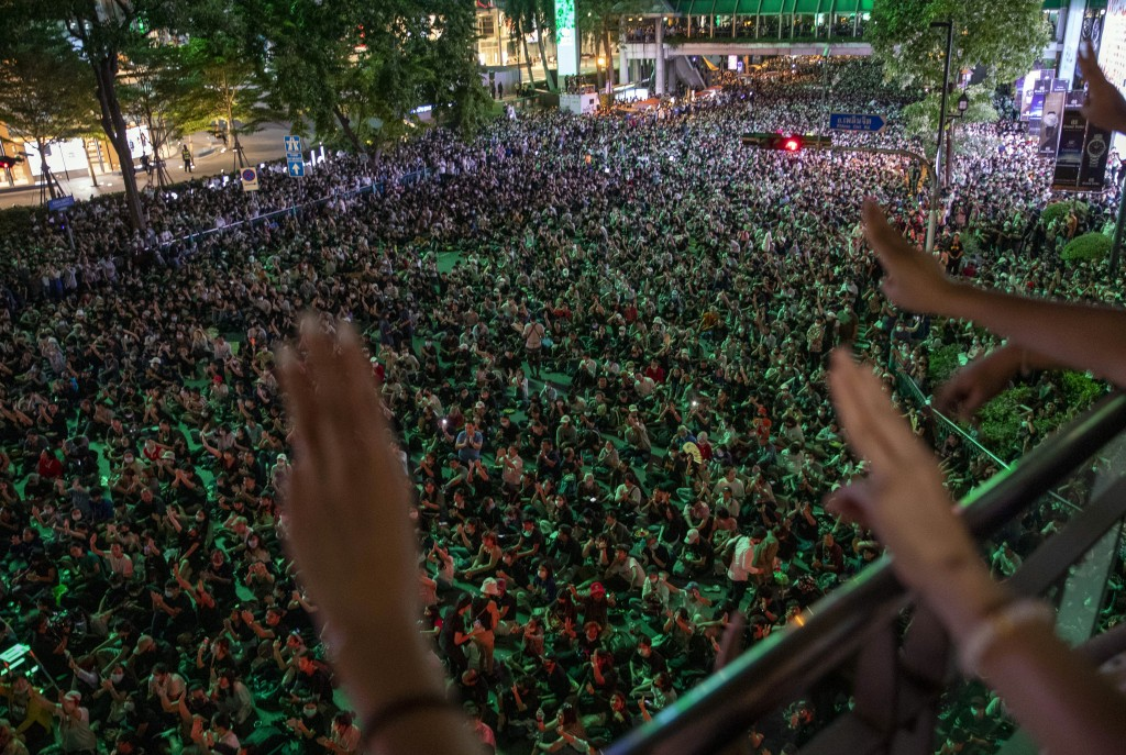 Pro-democracy protesters flash three-finger salutes, a symbol of resistance, during the pro-democracy rally occupied the main road in the central busi...