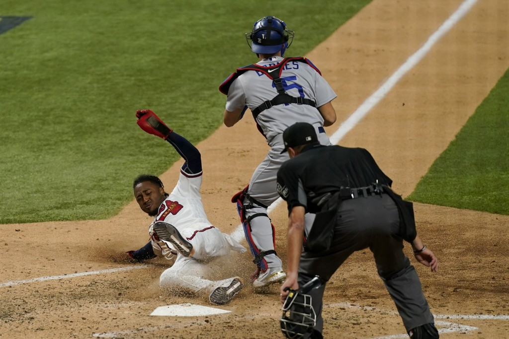 Atlanta Braves' Ozzie Albies scores past Los Angeles Dodgers catcher Austin Barnes on a double by Dansby Swanson during the sixth inning in Game 4 of ...