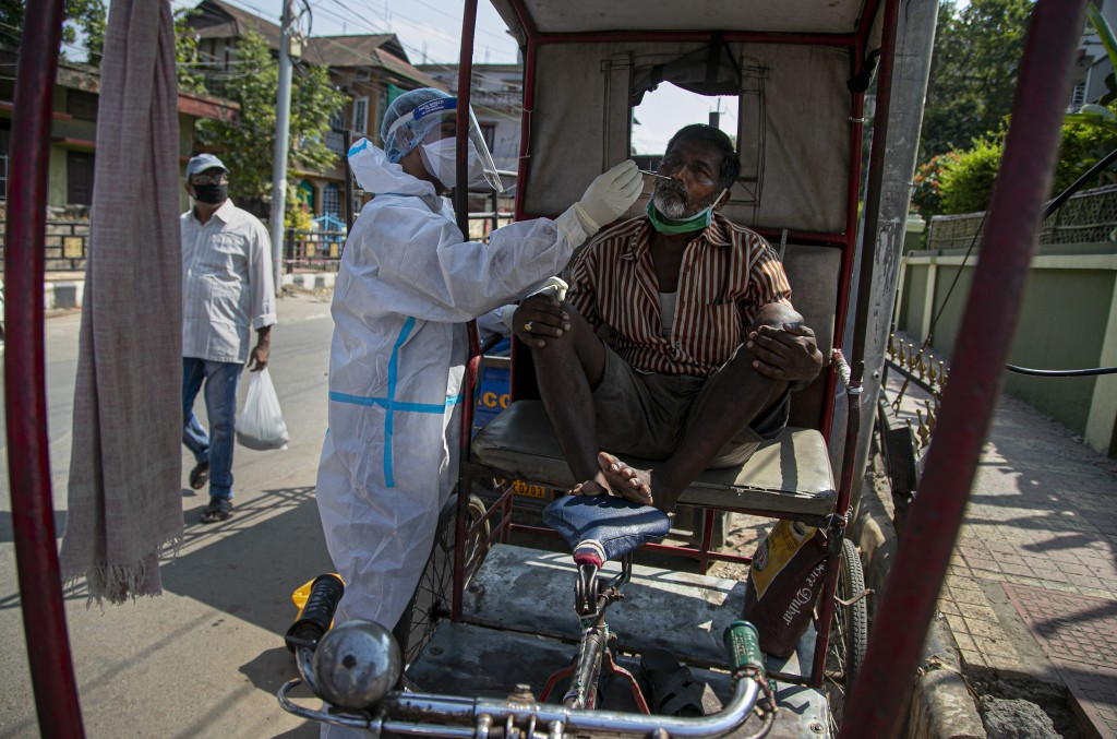 A health worker takes a nasal swab sample of a rickshaw driver during random testing for COVID-19 in a market in Gauhati, India, Friday, Oct. 16, 2020...