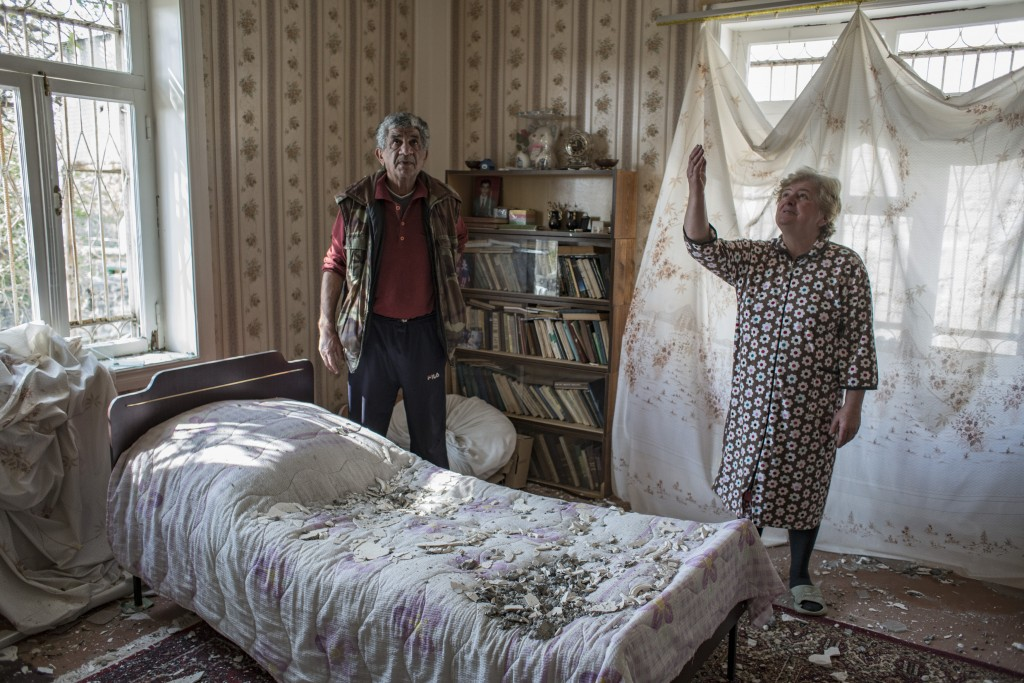 Nazile Tehmezova, right, and her husband Ramiz Huseyinov inspect the damage to their house following overnight shelling by Armenian forces, in the cit...