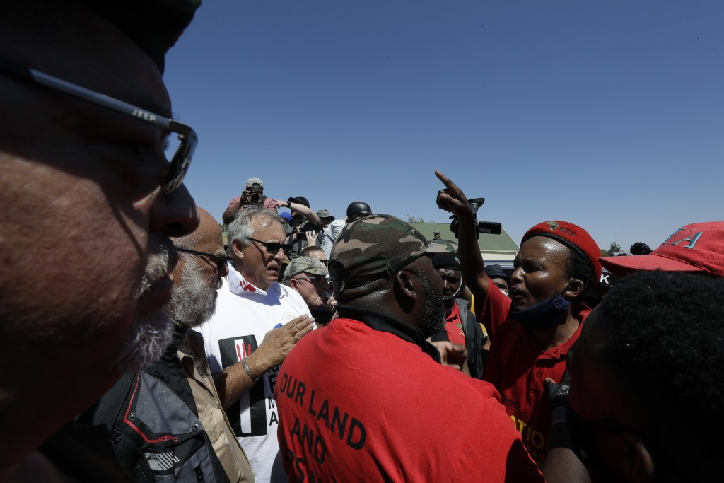 Members of the Economic Freedom Fighters, right, confront farmers, left, outside the magistrates court in Senekal, South Africa, Friday, Oct. 16, 2020...