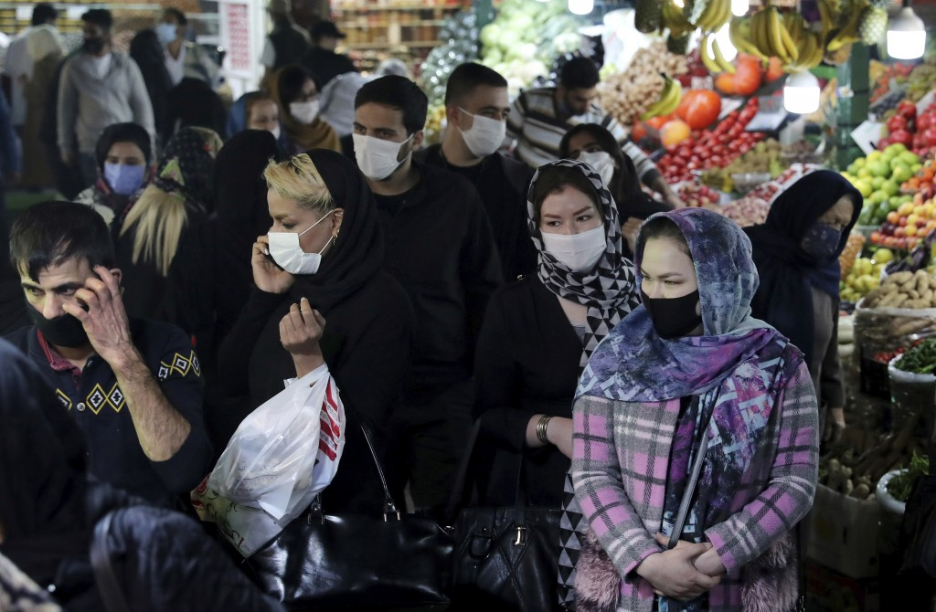 People wear protective face masks to help prevent the spread of the coronavirus in the Tajrish traditional bazaar in northern Tehran, Iran, Thursday, ...