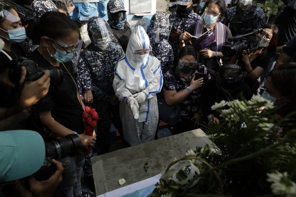 Detained left-wing activist Reina Mae Nasino in handcuffs and wearing a protective suit to prevent the spread of the coronavirus sprinkles holy water ...