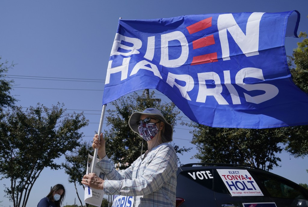 A Michell Rawlins shows her support of Democratic presidential candidate former Vice President Joe Biden by holding a flag in the wind Sunday, Oct. 11...