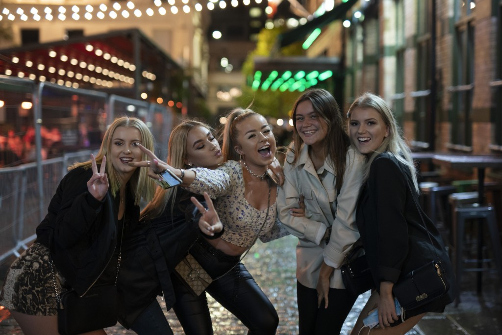 Young people pose for a photo, outside a bar in Liverpool, England, Monday Oct. 12, 2020. The English port city that gave the world the Beatles weathe...
