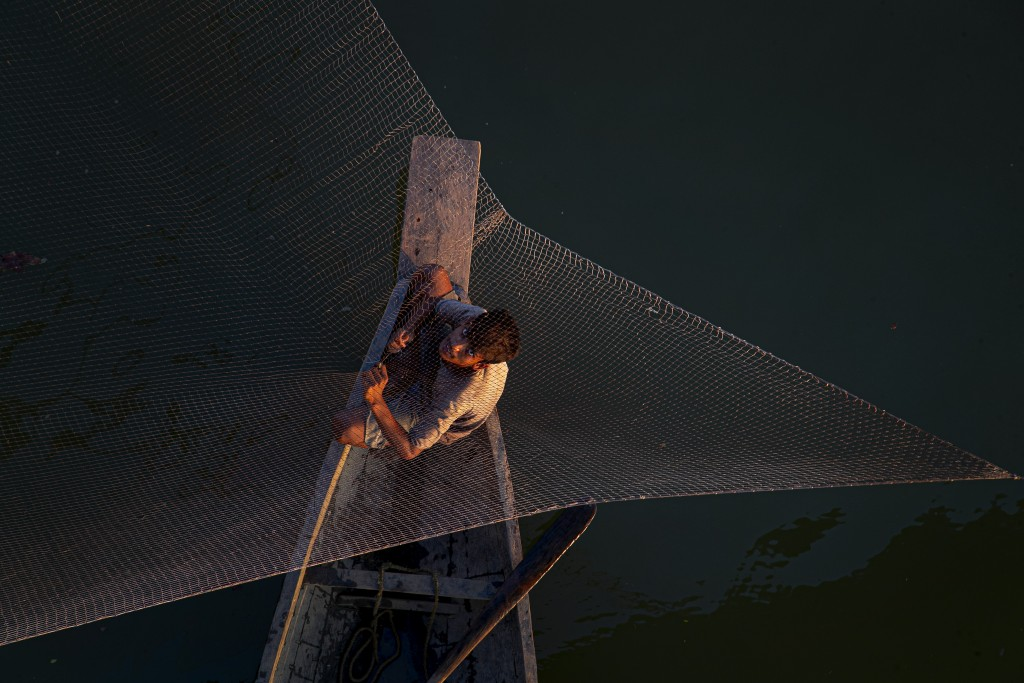 An Indian fisherman fixes his fishing net sitting on a country boat on the outskirts of Gauhati, India, Wednesday, Oct. 14, 2020. (AP Photo/Anupam Nat...