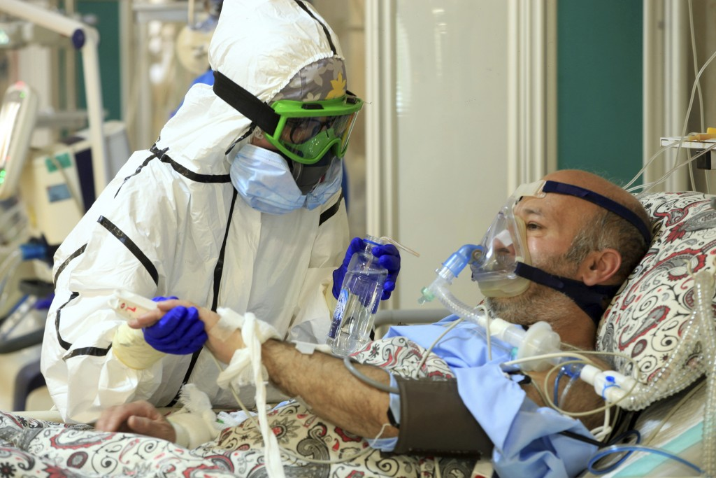 In this Wednesday, Oct. 14, 2020, photo provided by the Iranian Health Ministry, a medic tends to a COVID-19 patient at the Shohadaye Tajrish Hospital...