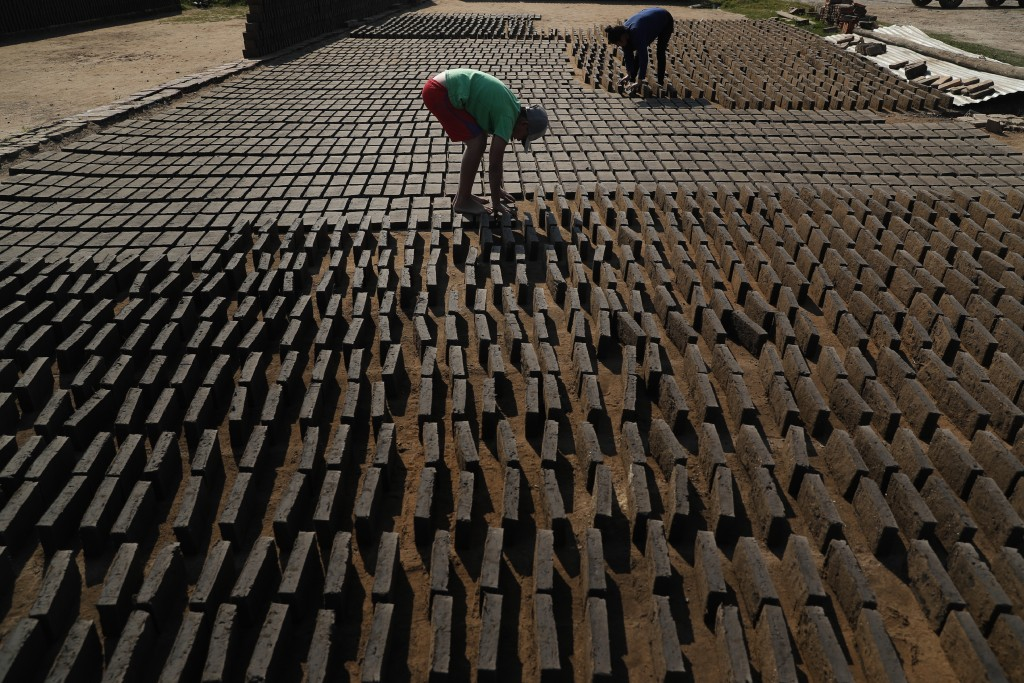 Cristian, center, turns clay bricks on their sides as they sun dry before they are put in a kiln at a small brick factory in Tobati, Paraguay, Monday,...