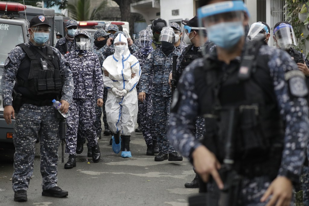 Police escort detained left-wing activist Reina Mae Nasino in handcuffs and wearing a protective suit to prevent the spread of the coronavirus walks a...