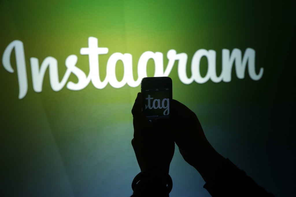 FILE - In this June 20, 2013 file photo, a journalist makes a video of the Instagram logo using the new video feature at Facebook headquarters in Menl...