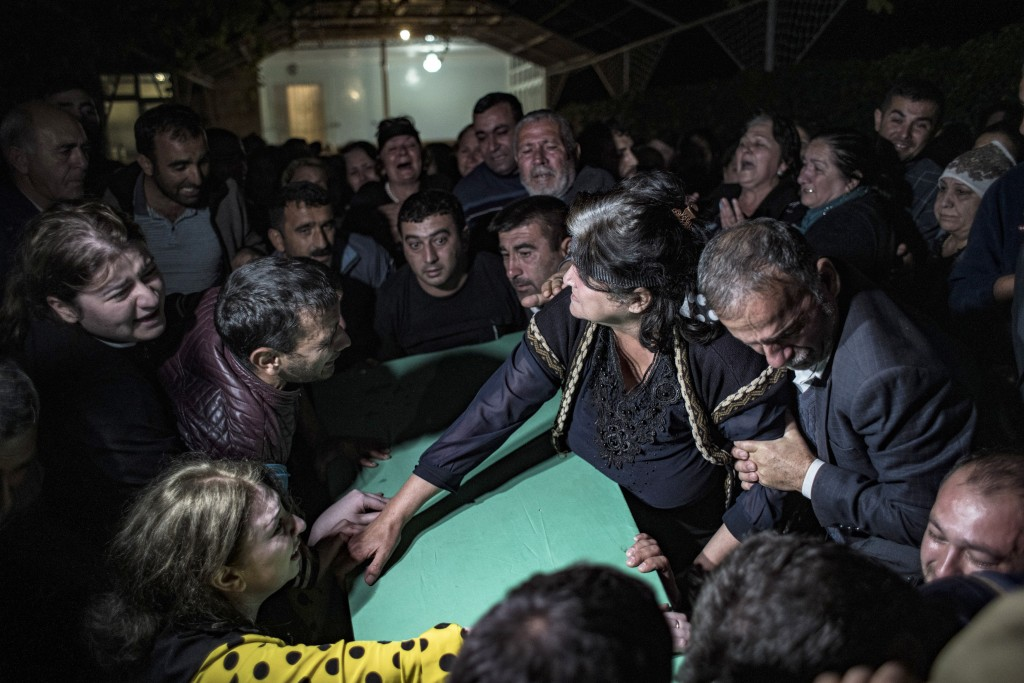 Family members mourn over the coffin of Parviz Orucoglu, a 29 year-old Azerbaijani Turk killed with three others in a shelling in a cemetery by Armeni...
