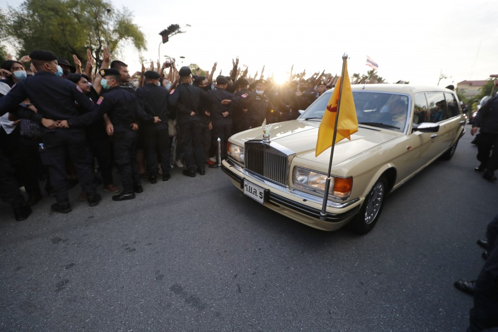 A vehicle with members of the Thai royal family onboard passes through a road where anti-government protesters gathered outside the Government House o...