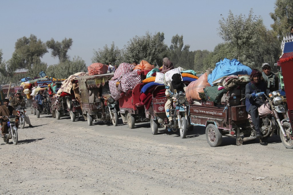 Afghan families leave their houses after fighting between the Afghan military and Taliban insurgents in Helmand province, southern of Afghanistan, Tue...