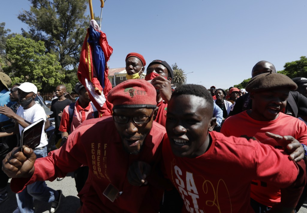 Members of the Economic Freedom Fighters protest outside the magistrates court in Senekal, South Africa, Friday, Oct. 16, 2020, where two suspects wer...
