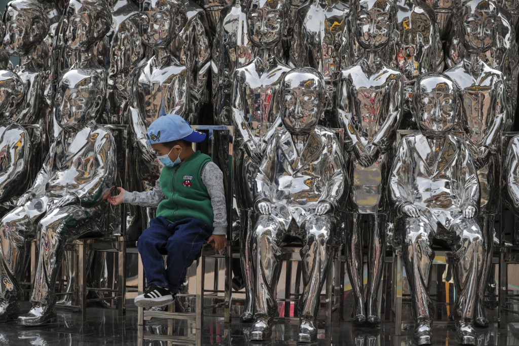 A child wearing a face mask to help curb the spread of the coronavirus tries to hold a statue's hand as he sits in an art installation on display at a...