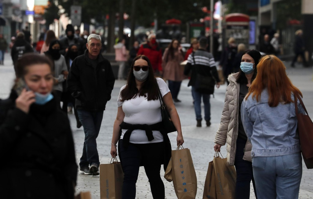 People walk down a shopping street in Liverpool, England, Wednesday, Oct. 14, 2020. As the first area in England slapped with strict new restrictions ...