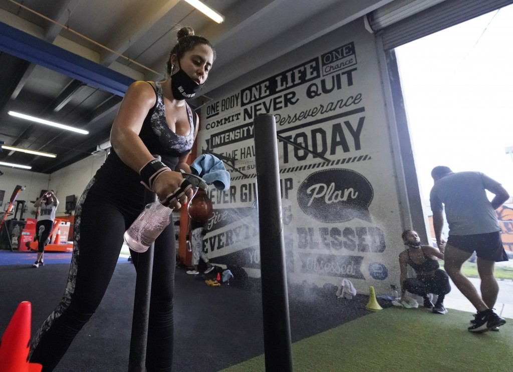 Giannina Nicoletti sanitizes a piece of equipment as she works out, Monday, Aug. 31, 2020, at Legacy Fit in the Wynwood Art District of Miami. As the ...