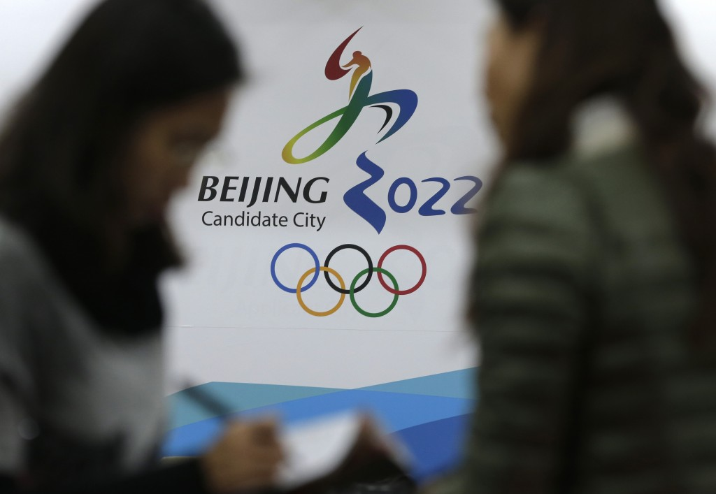 In this Nov. 4, 2014, file photo, journalists chat near the Beijing's bid for the 2022 Winter Olympics logo after attending a media briefing at the Be...