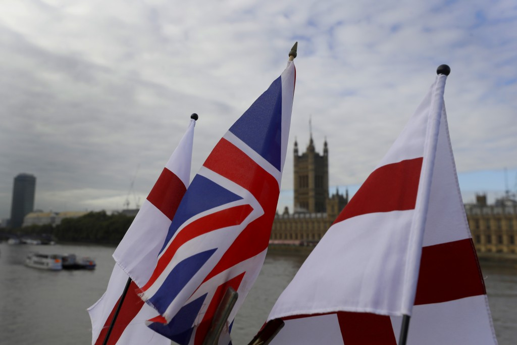 English flags and a Union flag fly above a souvenir stand opposite Britain's Parliament in London, Friday, Oct. 16, 2020. Britain's foreign minister s...