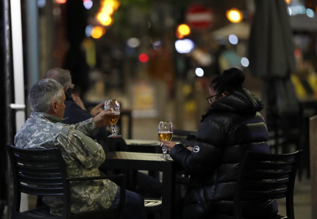 People drink a beer outside a restaurant in Liverpool, England, Wednesday, Oct. 14, 2020. As the first area in England slapped with strict new restric...