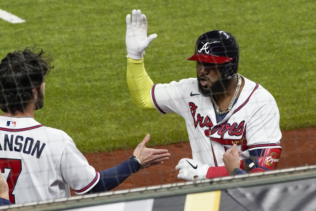 Atlanta Braves' Marcell Ozuna celebrates after a home run against the Los Angeles Dodgers during the fourth inning in Game 4 of a baseball National Le...