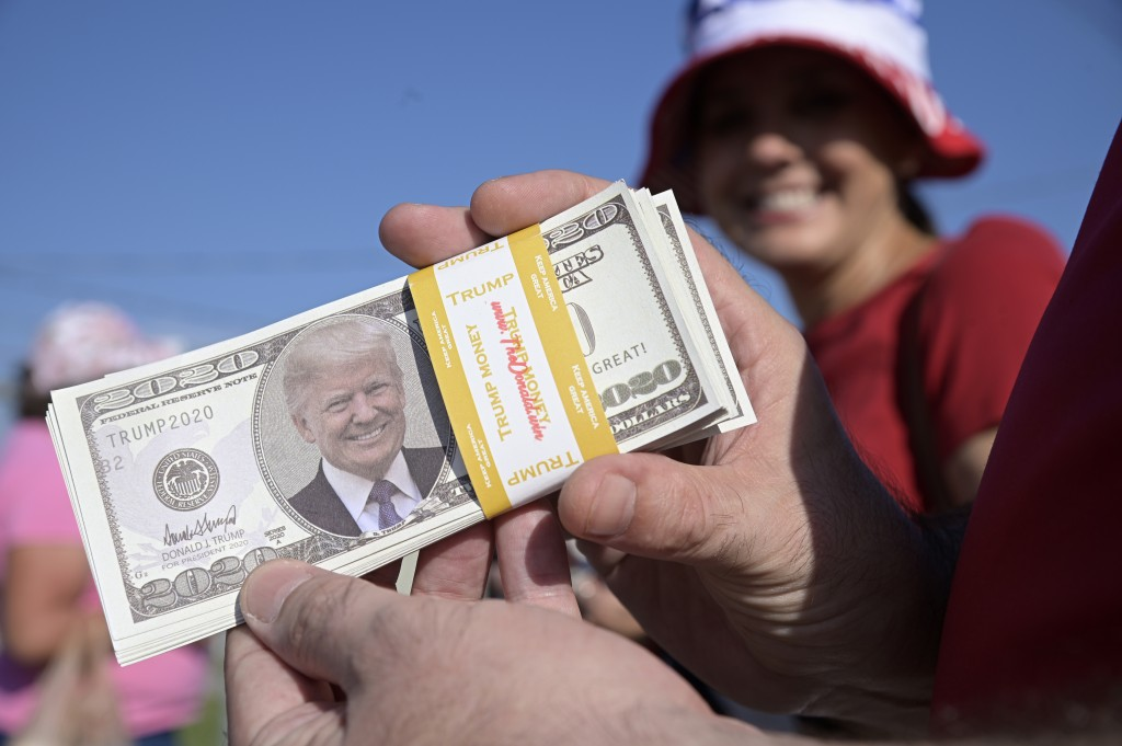 Kevin Miltenberger hands out imitation money with the likeness of President Donald Trump before a campaign rally at the Ocala International Airport, F...