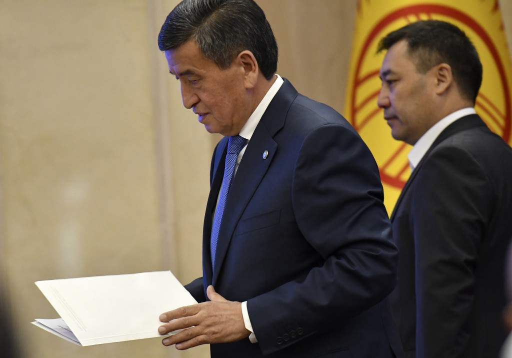 Kyrgyzstan President Sooronbai Jeenbekov walks holding a text of his resignation prior to addressing the Kyrgyzstan Parliament during the transfer of ...