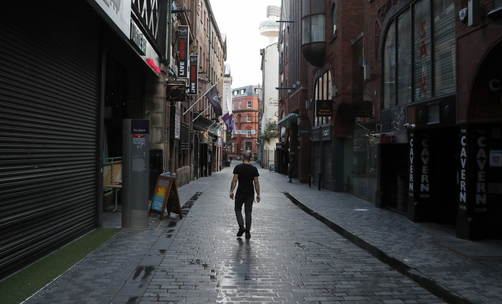 A lone man walks, past the famous Cavern club and other closed pubs and bars as new anti-coronavirus measures are set to come into force in Liverpool,...