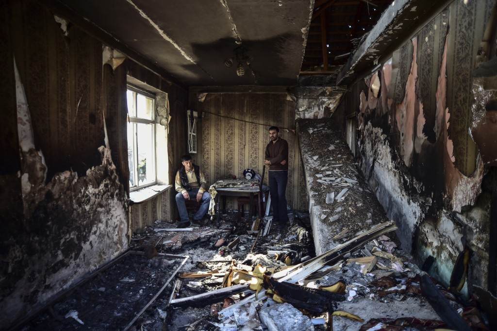 Men look at the damage in a house a day after four Azerbaijani Turks were killed and several others were wounded in a shelling in a cemetery by Armeni...