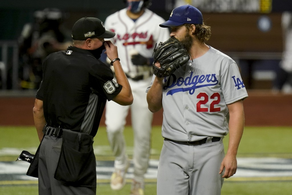 Los Angeles Dodgers starting pitcher Clayton Kershaw talks with home plate umpire Cory Blaser during the first inning in Game 4 of a baseball National...
