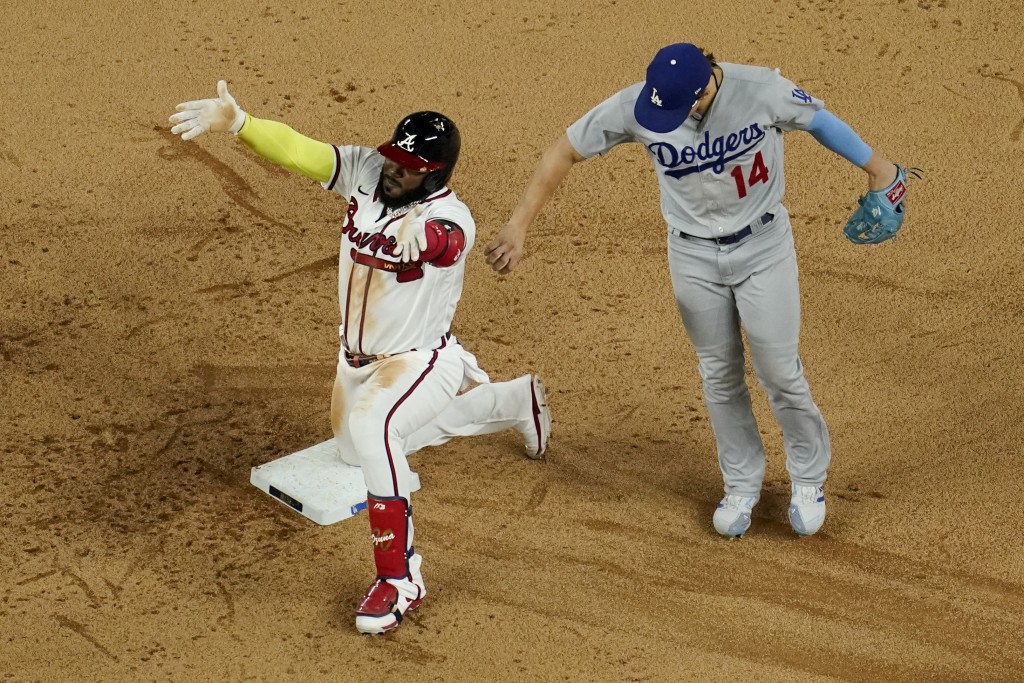 Atlanta Braves' Marcell Ozuna celebrates a RBI-double past Los Angeles Dodgers left fielder Enrique Hernandez during the sixth inning in Game 4 of a b...