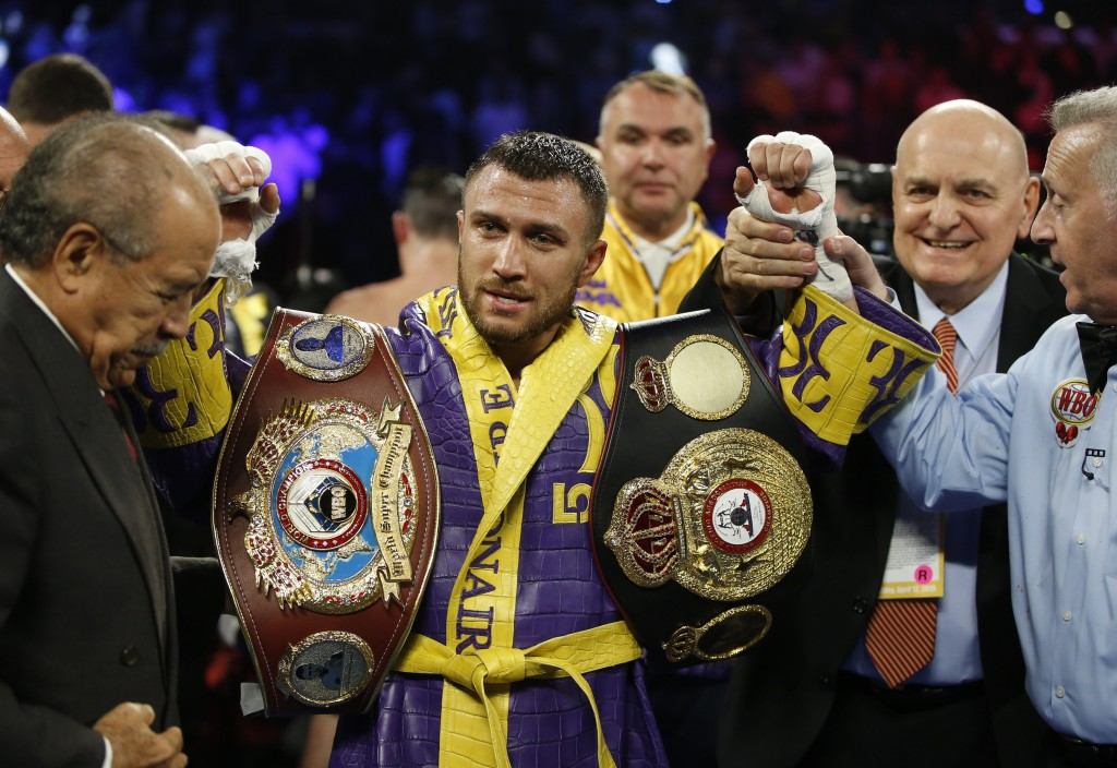 FILE - In this April 12, 2019, file photo, Vasiliy Lomachenko celebrates defending his WBA/WBO lightweight titles after knocking out Anthony Crolla, i...