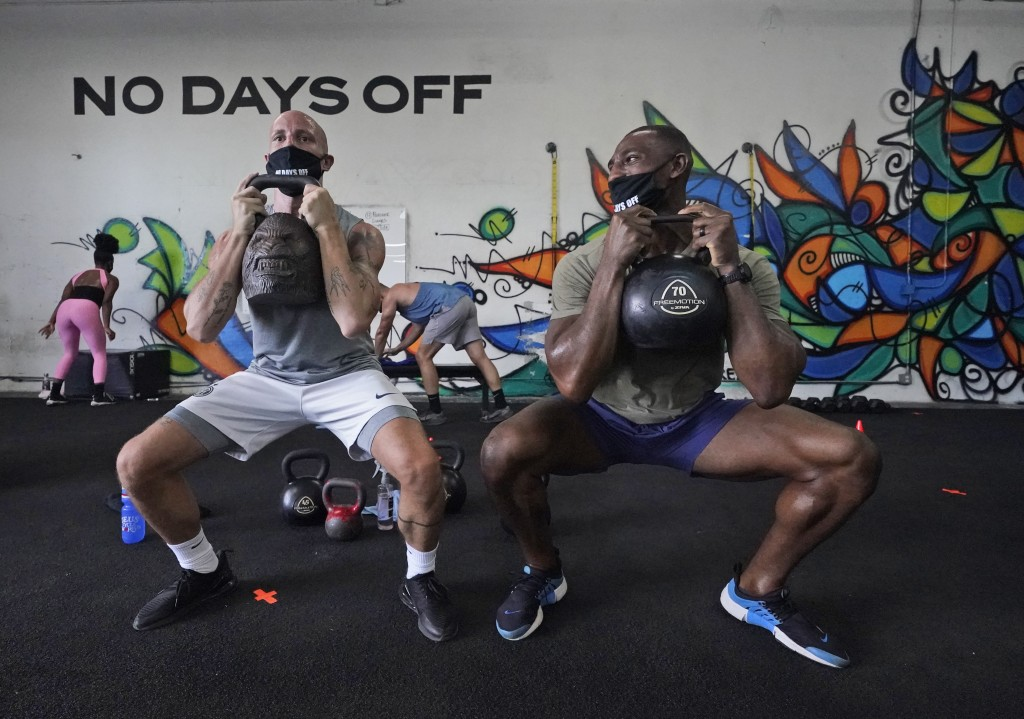 Trainer Xavier Aller, right, encourages Denis Musano as they lift kettlebell weights, Monday, Aug. 31, 2020, at Legacy Fit in Miami. As the vast major...
