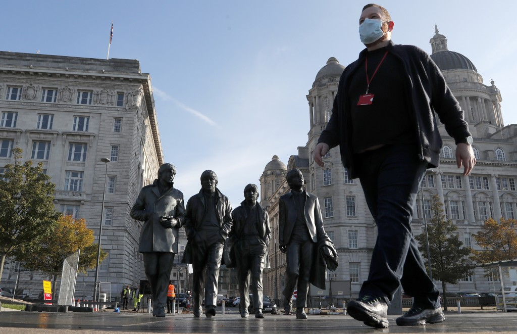John Ambrose, a guide with the Beatles-themed Fab4 Taxi Tours, wears a face mask as he walks past a statue of the Beatles in Liverpool, England, Wedne...