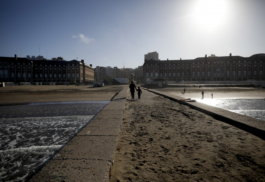 A woman and child walk along the coast during the COVID-19 pandemic in Mar del Plata, Argentina, Saturday, Oct. 10, 2020. The resort's new reality is ...