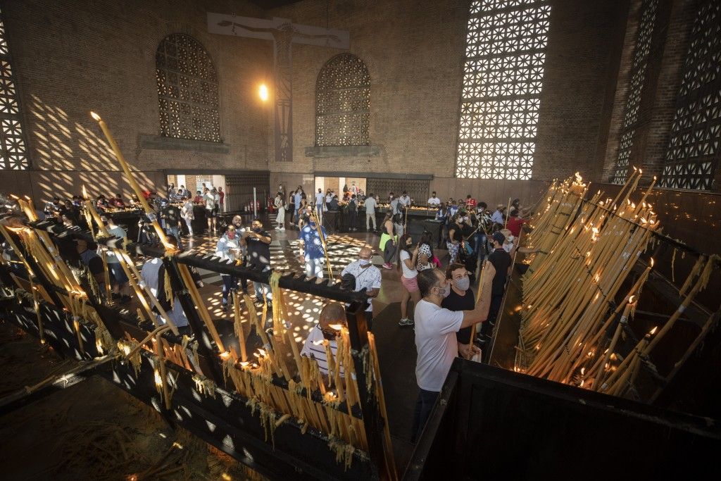 People light candles inside the candle room of Our Lady of Aparecida Basilica, the temple of Brazil's patron saint on her feast day in Aparecida, Braz...