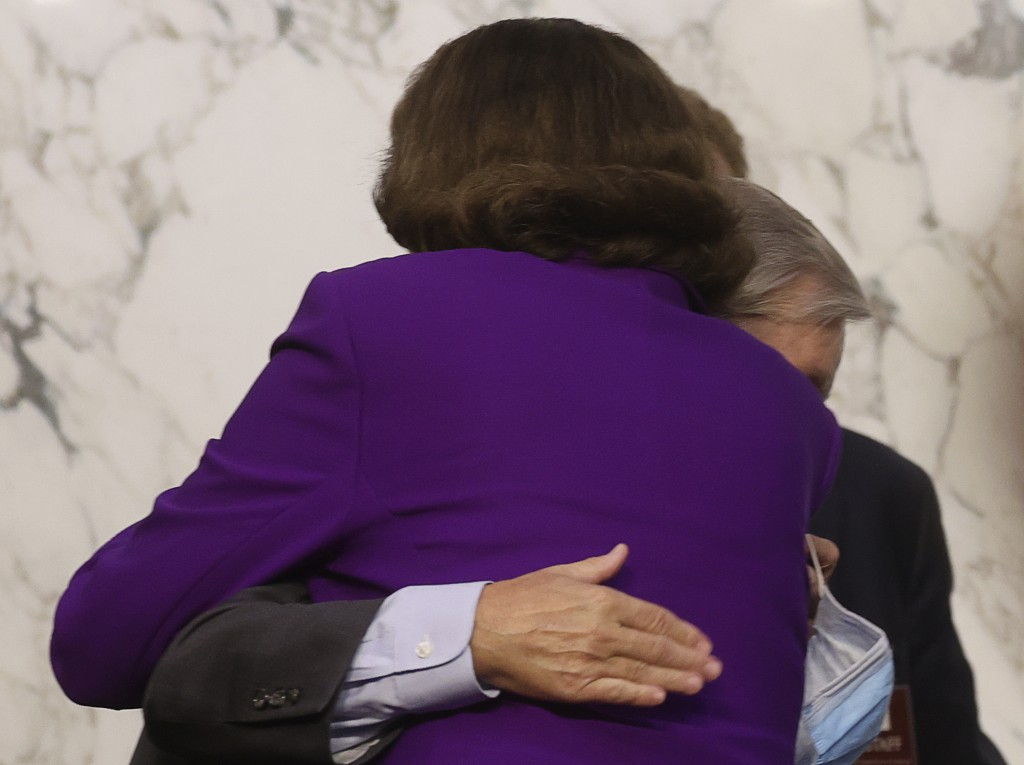 Sen. Lindsey Graham, R-S.C., hugs Sen. Dianne Feinstein, D-Calif., following the fourth day of a confirmation hearing for Supreme Court nominee Amy Co...