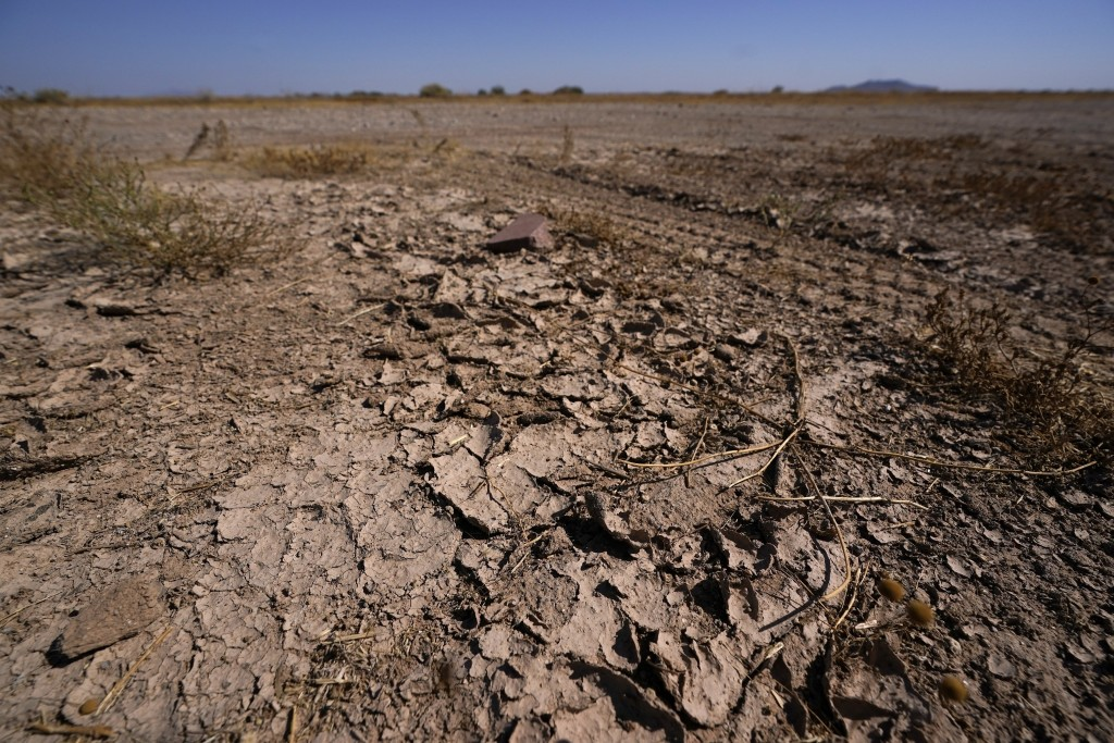 FILE - In this Wednesday, Sept. 30, 2020 file photo, dry desert soil cracks due to the lack of monsoon rainfall in Maricopa, Ariz. In a report release...