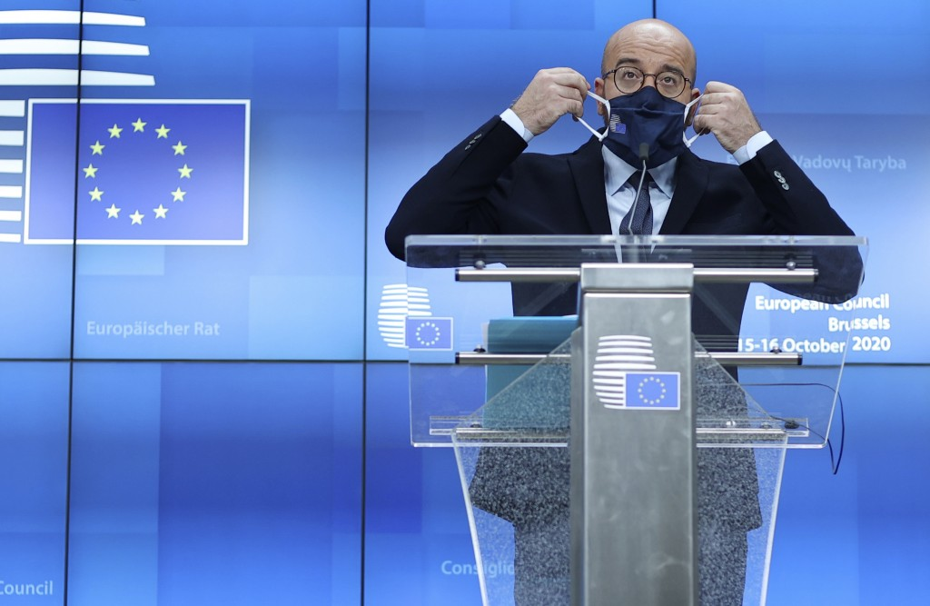 European Council President Charles Michel puts on his protective face mask after speaking during a media conference at an EU summit in Brussels, Thurs...