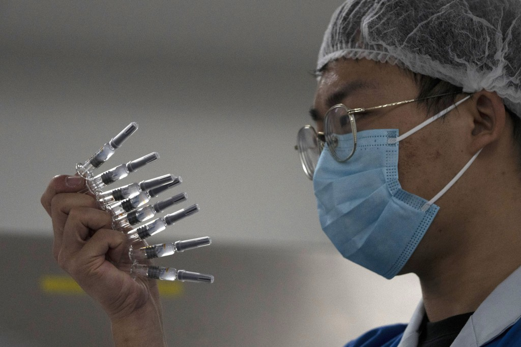 In this Sept. 24, 2020, file photo, an employee manually inspects syringes of the SARS CoV-2 Vaccine for COVID-19 produced by Sinovac at its factory i...