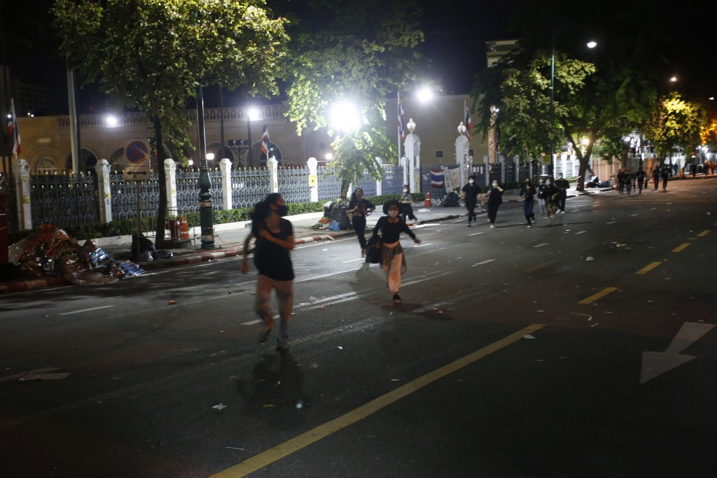 Pro-democracy protesters run away from riot police during a demonstration in Bangkok, Thailand, Thursday, Oct. 15, 2020. Thai police dispersed a group...